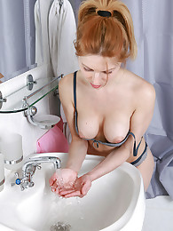 Hot busty redhead getting naked in her bathroom preparing to shower