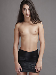 18 year old Georgia sheds her sleek black leather miniskirt and poses nude gazing into the camera with emerald green eyes