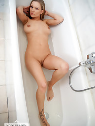 Naked Daisy is having fun in the bath. She pushes her firm breasts, lolling around in the water and show everything for you.