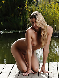 Mona is a top babe spending a beautiful day near the lake. Join this blonde hottie, fully nude and relaxing in the sun, she is waiting for you..